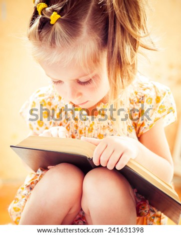 sweet happy little girl reading the book - stock photo