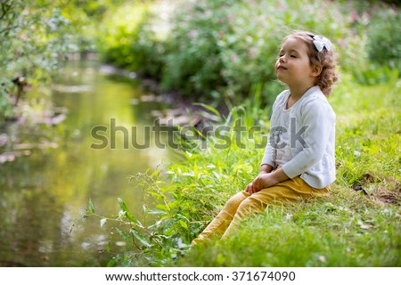 Sweet, happy little girl sitting on a grass in a park at a spring stream with flower in hand. Laughing, enjoying fresh air in forrest.  - stock photo