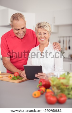 Sweet Happy Senior Couple Using their Tablet Computer While Preparing Something to Eat for Dinner at the Kitchen
