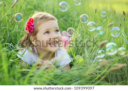 Sweet, happy, smiling three year old girl laying on a grass in a park playing with bubbles