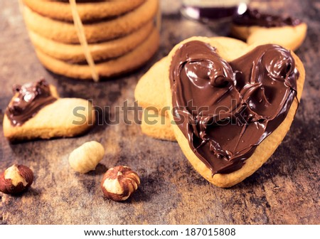 Sweet hazelnut cream and homemade cookies.Selective focus on the cookie with heart shape - stock photo