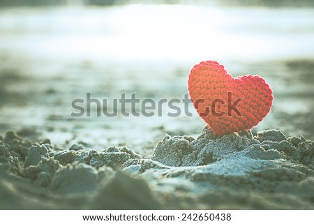 sweet heart on sand beach under sunset and warm light. abstract background love summer on the beach. vintage color tone. - stock photo