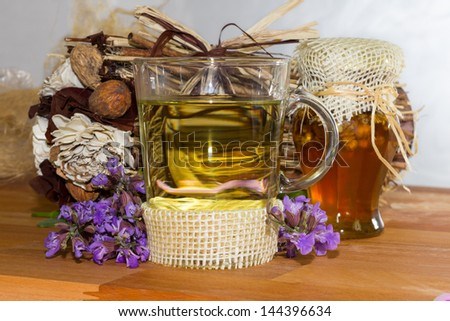 Sweet herbal Tea or infusion with honey and sage for cold winter days, helps to prevent to prevent sore throat. - stock photo