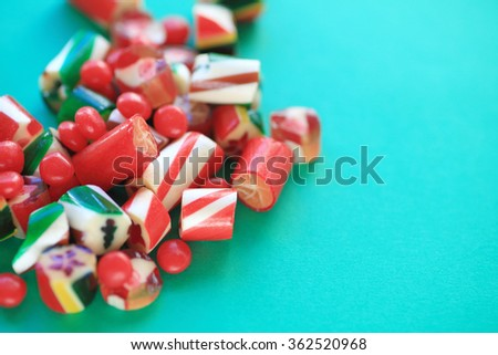 Sweet holiday hard candies on a green background with copy space - stock photo