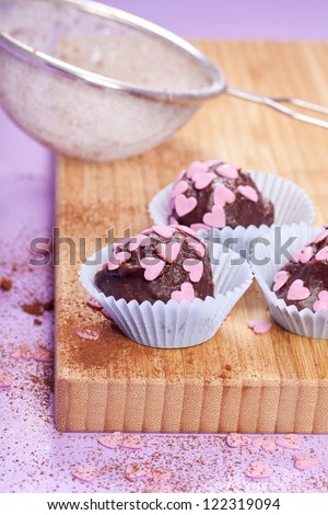 sweet homamade dark chocolate pralines with pink hearts - stock photo