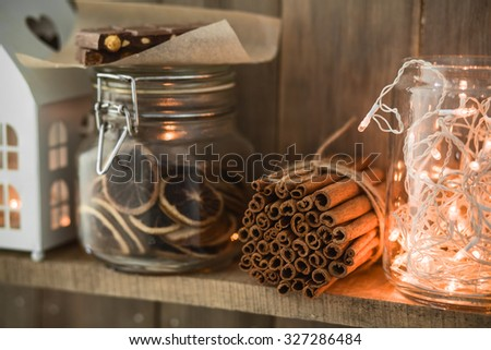 Sweet home. White Christmas decor on vintage natural wooden background. Cinnamon sticks and dried citrus. Cafe shelf. Selective focus. - stock photo