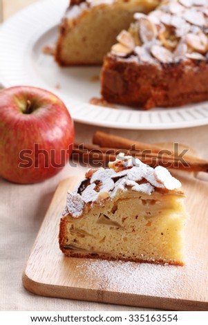 sweet homemade apple cake with almond on wooden plate