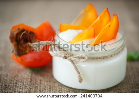 sweet homemade yogurt with persimmons in a glass jar - stock photo