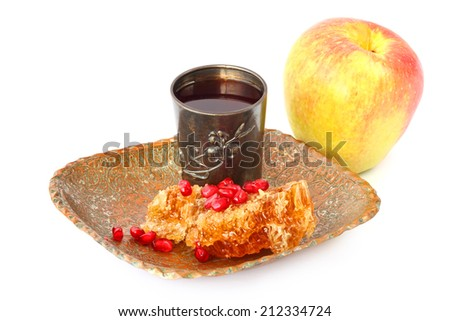 Sweet honey comb with honey, pomegranate grains, silver glass with wine and apple fruit - Jewish traditional food for the holiday of Rosh Hashana (Jewish new year). Isolated on a white background - stock photo