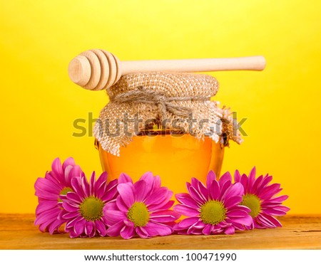 Sweet honey in jar with drizzler on wooden table on yellow background - stock photo