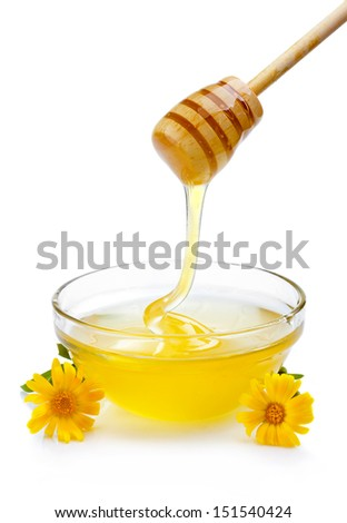 Sweet honey pouring from wooden dipper in glass bowl isolated on white - stock photo