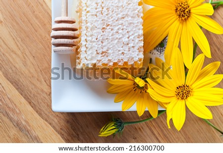 sweet honeycomb and yellow flowers on wooden table