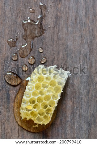 sweet honeycombs with honey isolated on old wooden background - stock photo