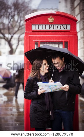 Sweet honeymoon couple consulting map in London - stock photo