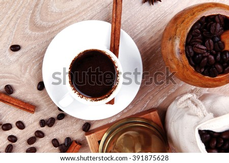 sweet hot drink : black arabic coffee in small white cup with mortar and pestle , bag full beans, copper old style cezve , decorated with cinnamon sticks and anise stars