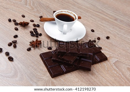 sweet hot drink : black Turkish coffee in small white mug with coffee beans spilled over a wooden table with stripes of dark chocolate and cinnamon stick - stock photo