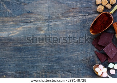 Sweet ingredients for hot chocolate and vintage scoop on dark wooden background with space for text. - stock photo
