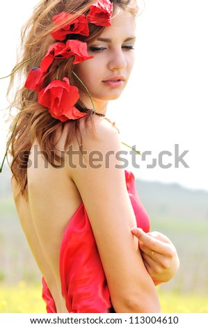 sweet lady standing with poppies in her hair - stock photo