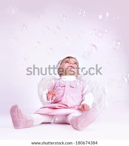 Sweet little angel sitting at the studio and playing with soap bubbles, having fun, wearing white fluffy wings, happy childhood concept  - stock photo