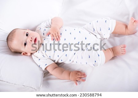 Sweet little baby boy is laying on his back. - stock photo