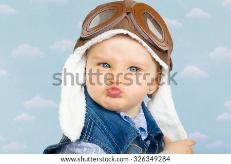 sweet little baby dreaming of being pilot - stock photo