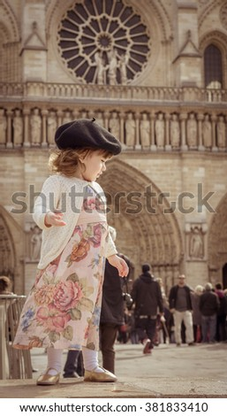 Sweet little baby girl (one year) with beret playing with doves in the cathedral of Notre Dame, Paris , France. Traveling with children. Beautiful and elegant pink dress and beret