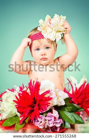 Sweet little baby girl sitting among flowers. Beauty, childhood. Healthcare. - stock photo
