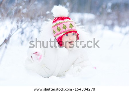Sweet little baby girl with beautiful blue eyes playing in snow in a beautiful park on a cold winter day - stock photo