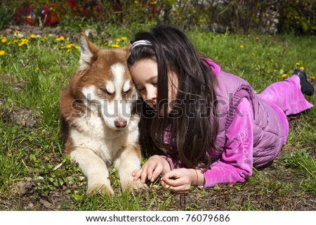 Sweet little baby husky on the grass with her little owner - stock photo
