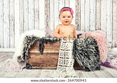 sweet little baby sitting in an old wooden crate with blanket
