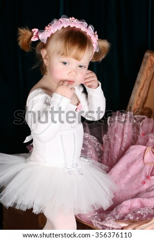 Sweet little ballet girl unpacking a suitcase with costumes - stock photo