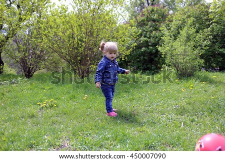 Sweet little blond girl child with blue eyes playing outdoors with curly hair in the wind.