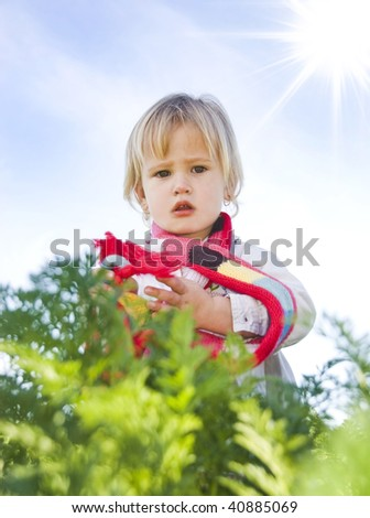 Sweet little blond girl outdoor with sun and sky in the background - stock photo