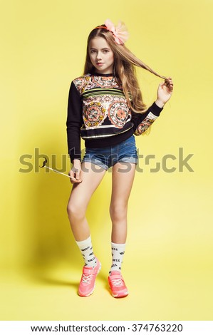 sweet little blonde girl in jeans shorts, sneakers, sweatshirt holding paper mustache. Kid fashion photo. Long hair style - stock photo