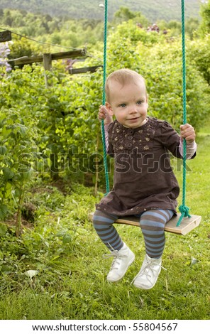 Sweet little blue eyed toddler on swing in a green garden - stock photo