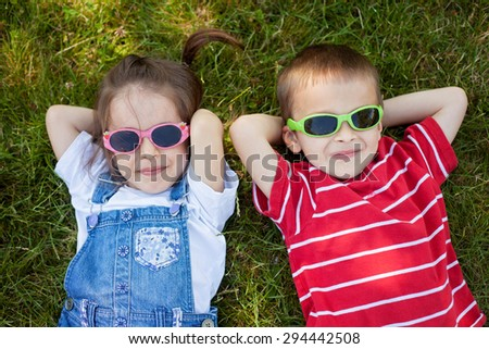 Sweet little boy and girl, wearing glasses, smiling, laying on the grass in the park