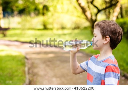 Sweet little boy drinking mineral water from the plastic bottle  in the park