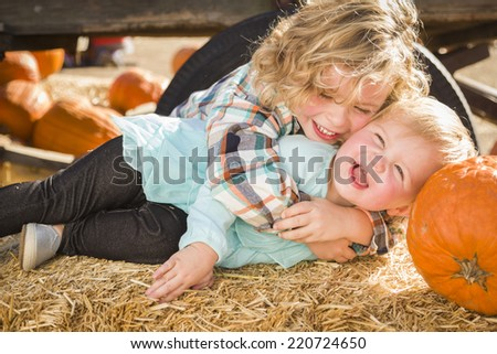 Sweet Little Boy Plays with His Baby Sister in a Rustic Ranch Setting at the Pumpkin Patch. - stock photo