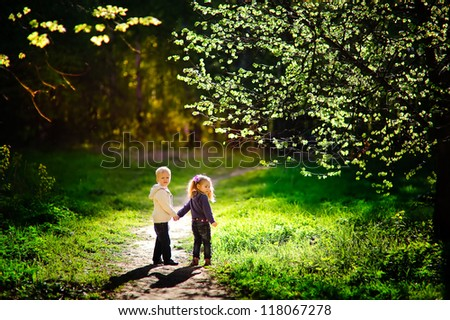 sweet little girl and boy have a date in beautiful park - stock photo