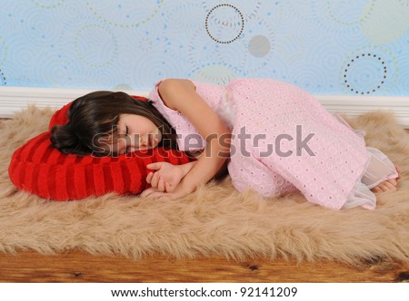 sweet little girl asleep on heart shaped valentine's pillow - stock photo