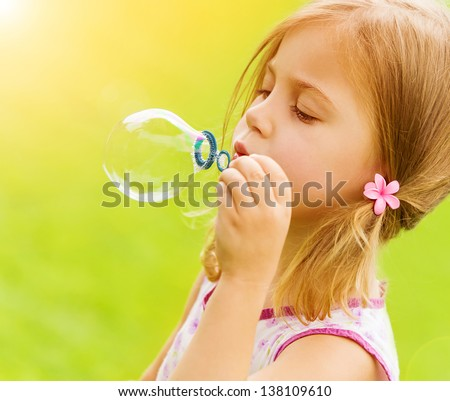 Sweet little girl blowing soap-bubbles in the garden, summer time, game outdoors, having fun, holiday concept - stock photo