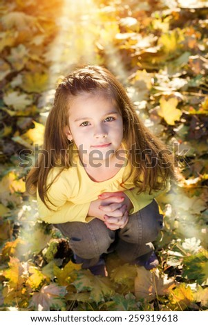 Sweet, little girl crouch in the autumn park, hands clasped for prayer, looking at camera.Sunset light falling on the little smiling little girl.Shallow doff, lens flare, high angle view - stock photo