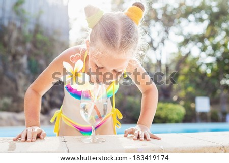 Sweet little girl drinking cocktail in tropical beach pool. Outdoors - stock photo