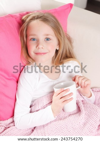 Sweet little girl drinking tea in the bed - stock photo