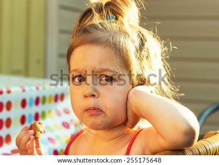 Sweet little girl eating cake at sunset - stock photo