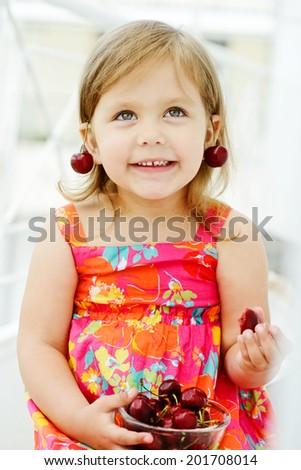 sweet little  girl eating merry - stock photo