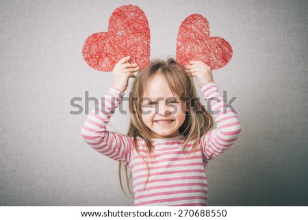 sweet little girl holds a valentines heart and thinks of love, isolated on gray background - stock photo