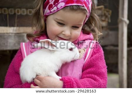 Sweet little girl hugs the baby rabbit - stock photo