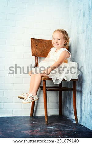 Sweet little girl in a beautiful white dress sitting on the old chair by the white brick wall. Childhood. - stock photo
