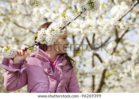 Sweet little girl in a blossom chery garden - stock photo